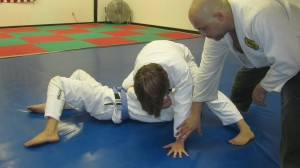 She begins to pivot around, moving her left hand from Paulo's head to the mat so she can spin her hips under his arm.