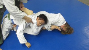 She finishes the submission by hooking Paulo's head with her right leg, controlling the wrist and driving her hips down.