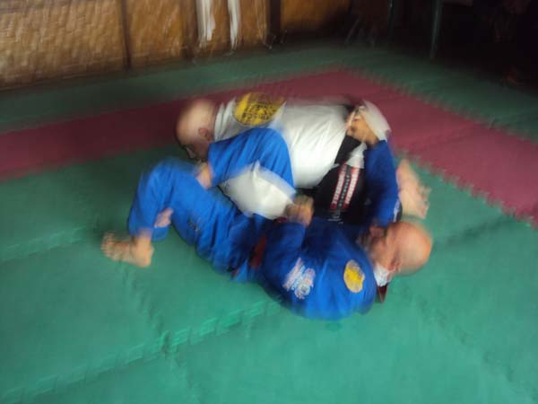 Manuel figure-fours his legs to trap Victor's left arm and grabs Victor's belt to prevent him from rolling out of the submission.