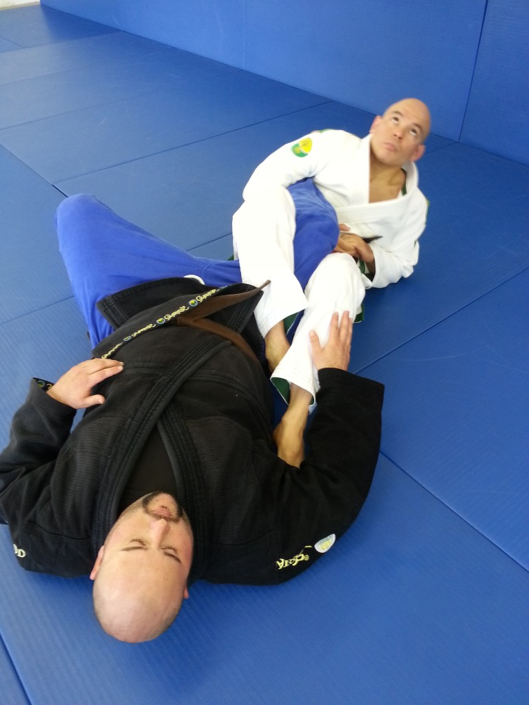 Step 6: Robert connects his hands under Big Bus' achilles, squeezes his knees together and lifts his hips to finish the straight ankle lock.